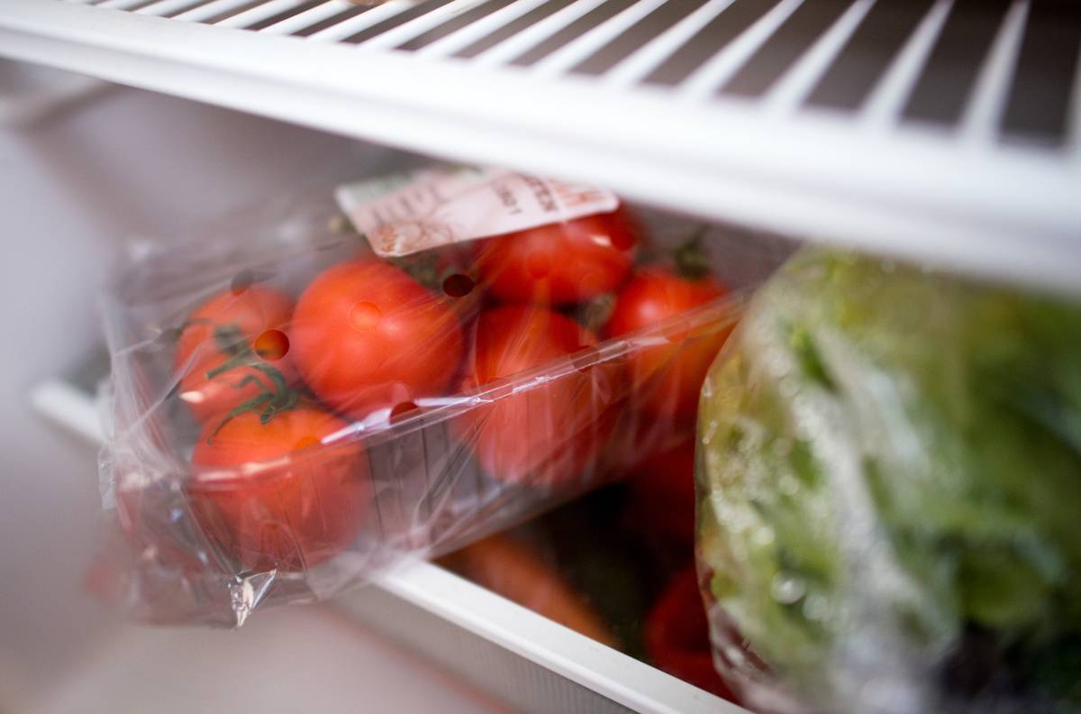 Packaged tomatoes are in a refrigerator drawer.