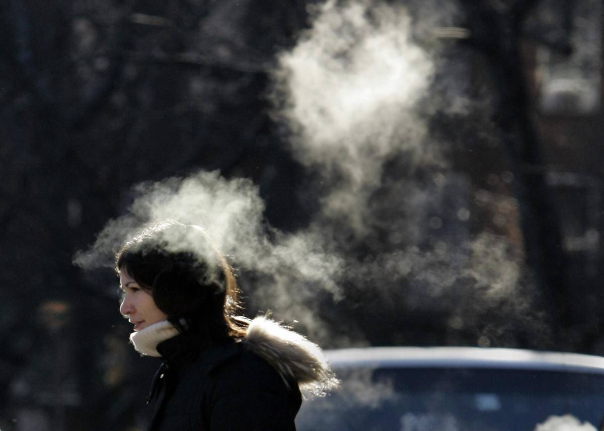 A woman's breath appears in the cold air.