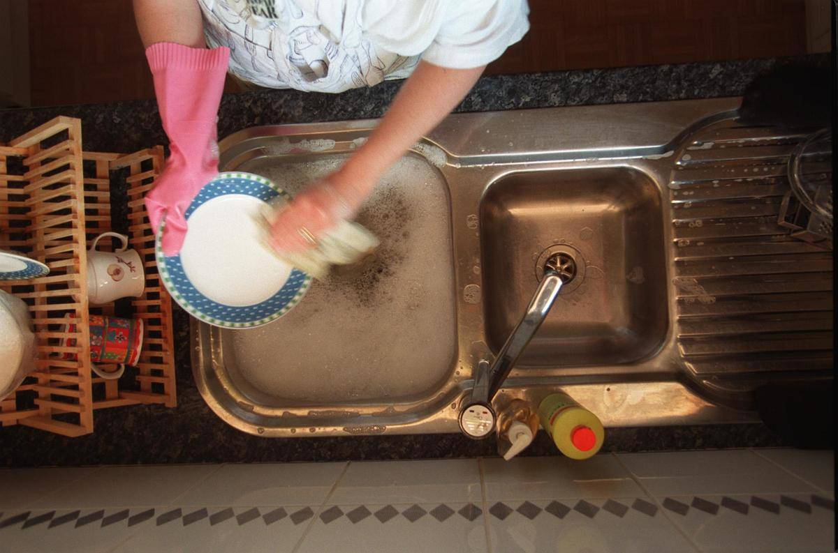 A woman hand-washes dishes.