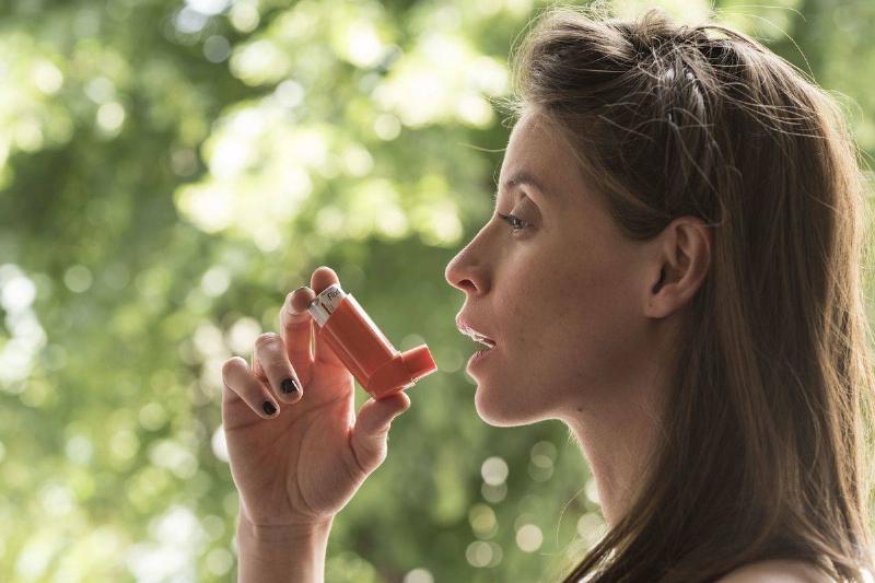 A woman uses an inhaler.