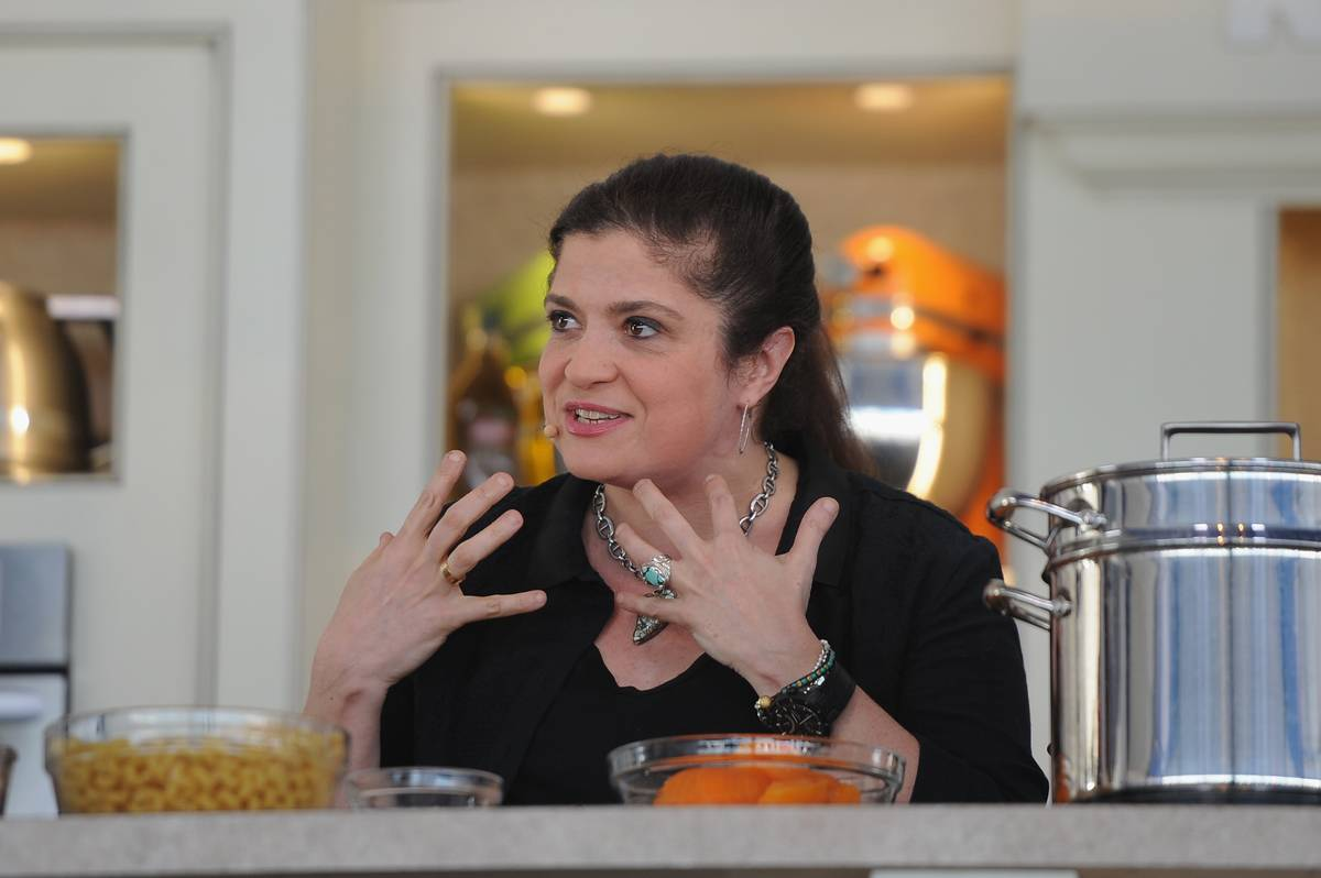 Alex Guarnaschelli prepares food dishes while she speaks passionately.