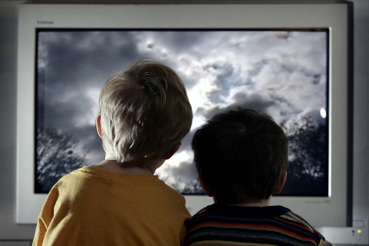 Two boys sit close to the TV.