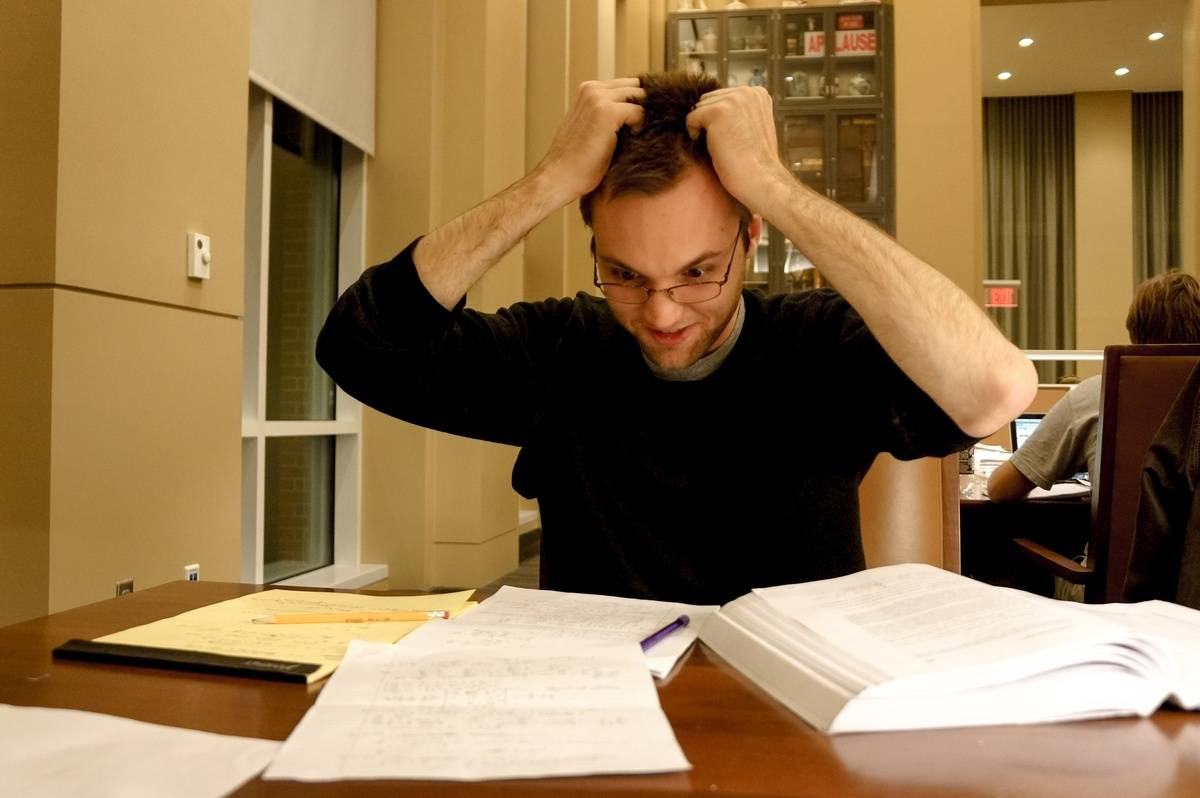 A frustrated student pulls at his hair while reading.