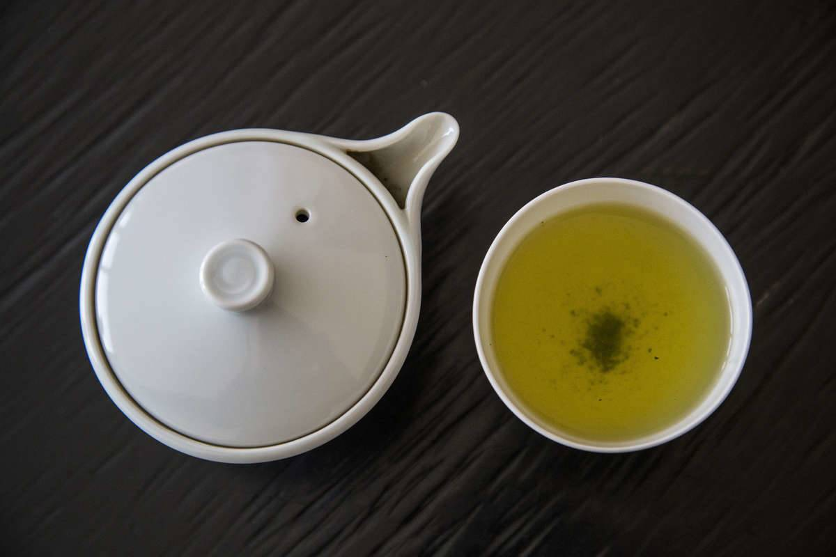 A teapot sits next to a cup of green tea.