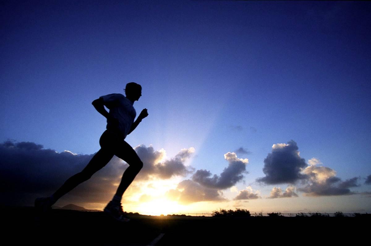 A man jogs as the sun rises.