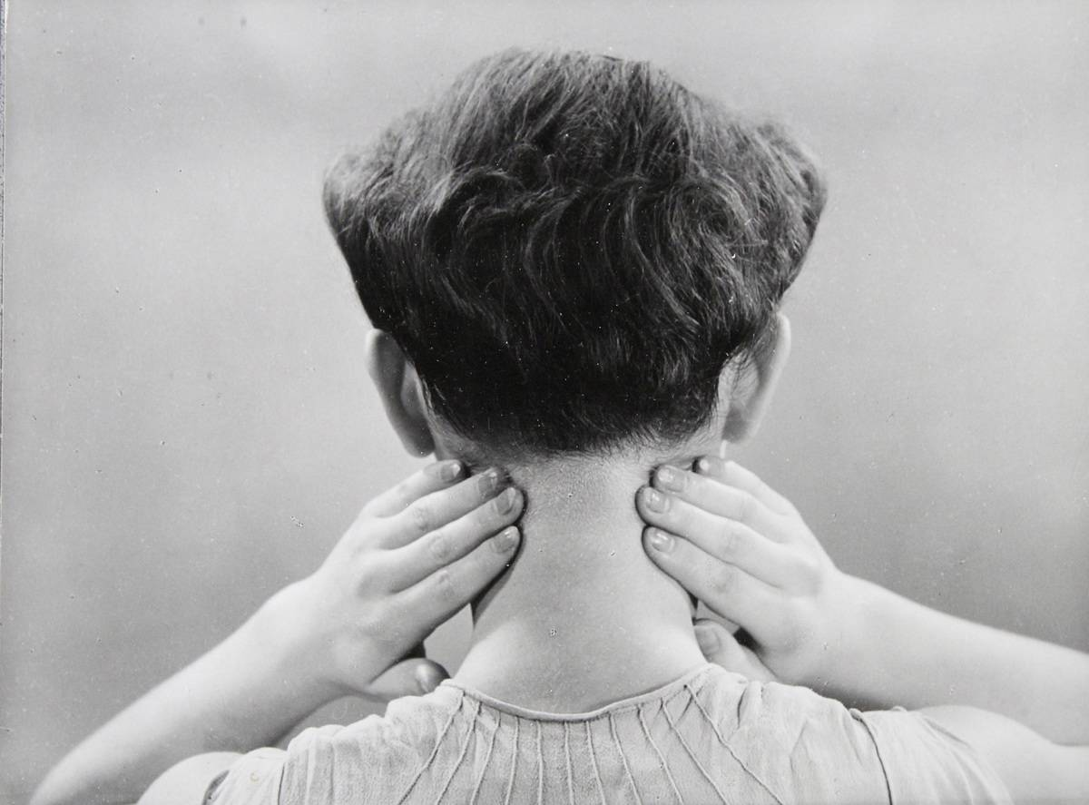 A man rubs the back of his neck.