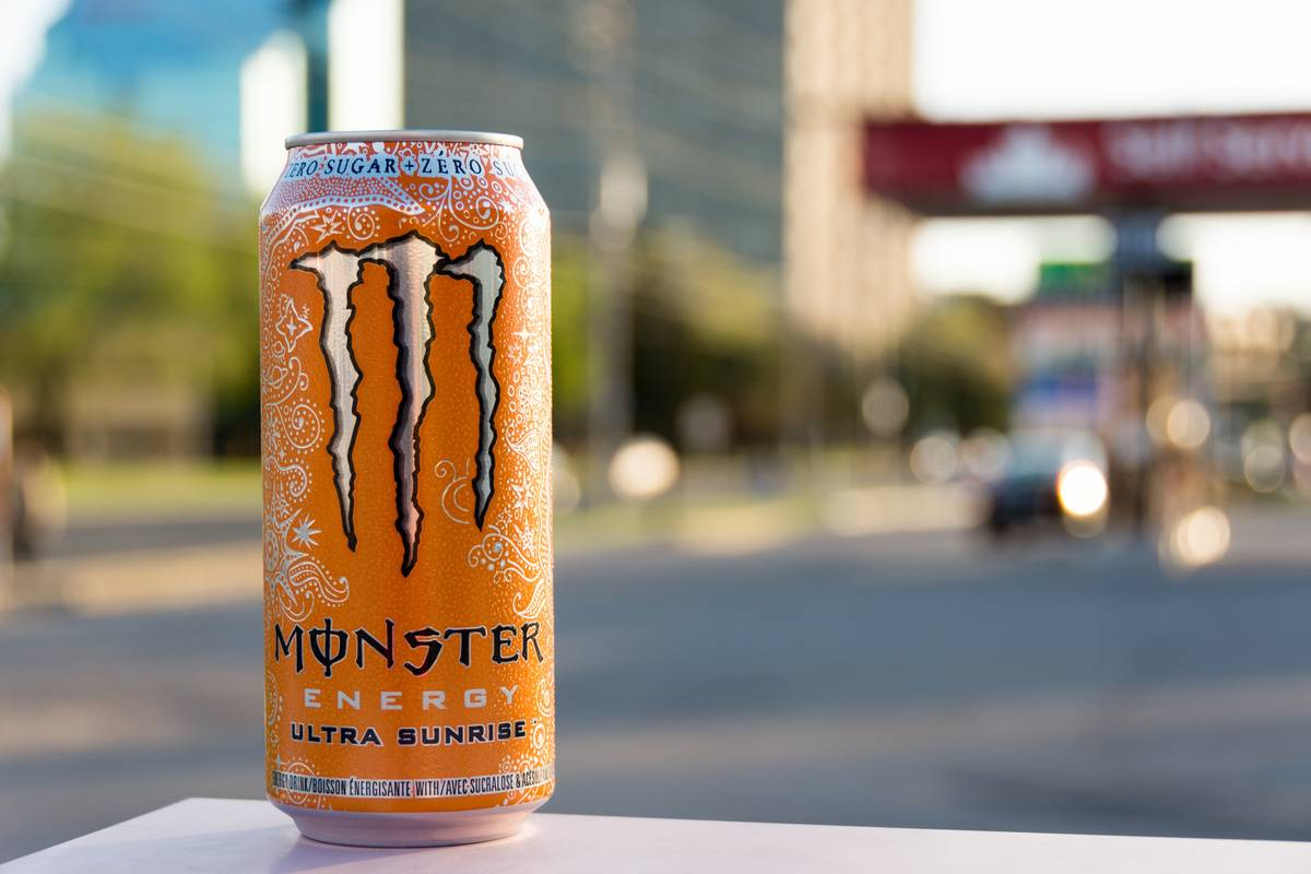 A can of Monster energy drink sits on a table.