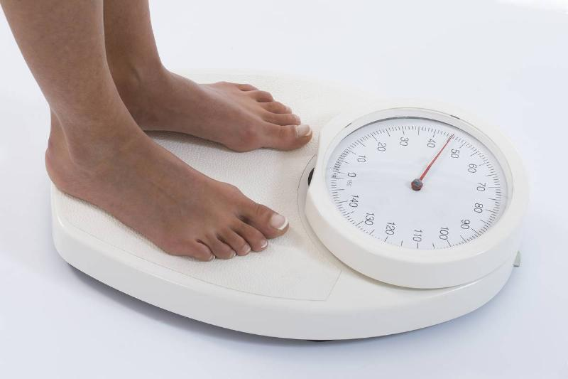 A woman steps onto a scale to weigh herself.
