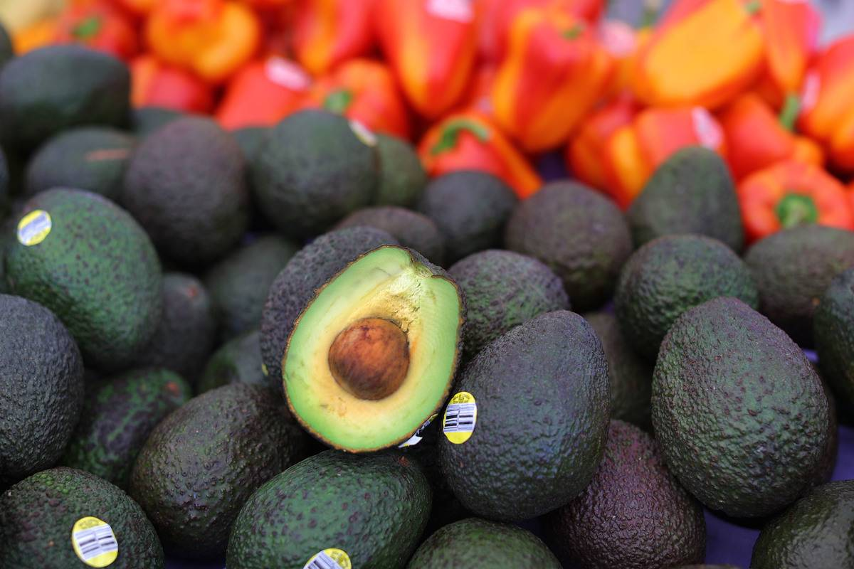 A cut open avocado is seen on a pile of whole avocados.
