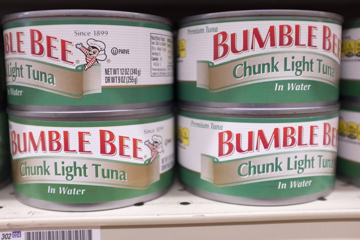 Four cans of tuna are stacked at a grocery store.