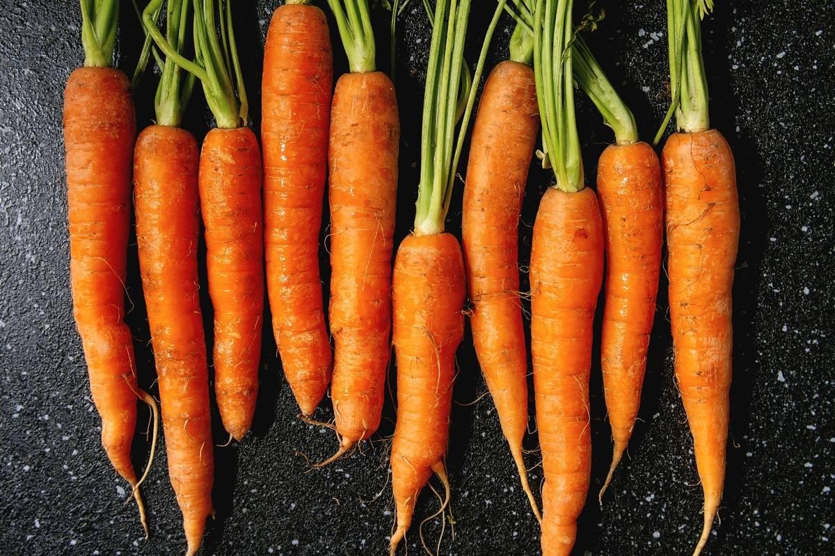 Whole carrots lie against a black background.