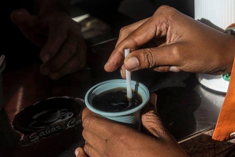 A woman stirs sugar into her mug of coffee.