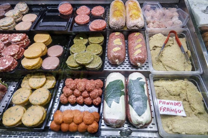 A variety of processed meats are on sale in a Portuguese deli.