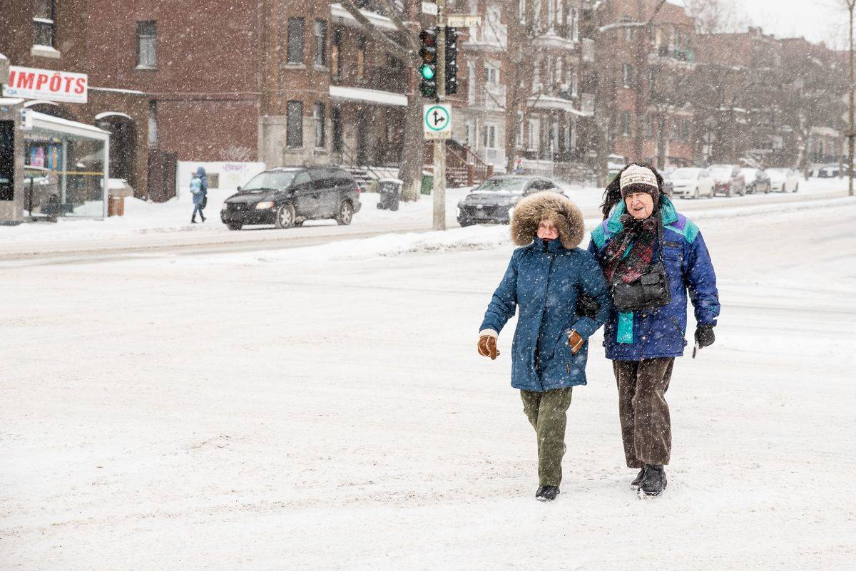 A couple walks in the snow while wearing large, warm coats.