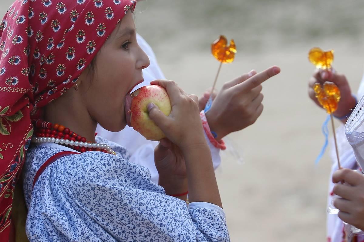 A girl eats an apple at a festival.