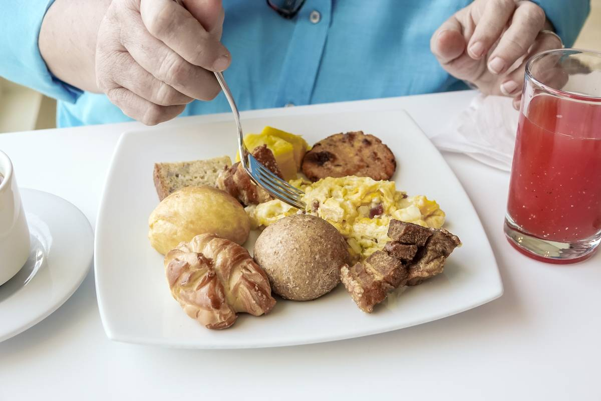 An elderly woman eats from a plate of eggs and pastries for breakfast.