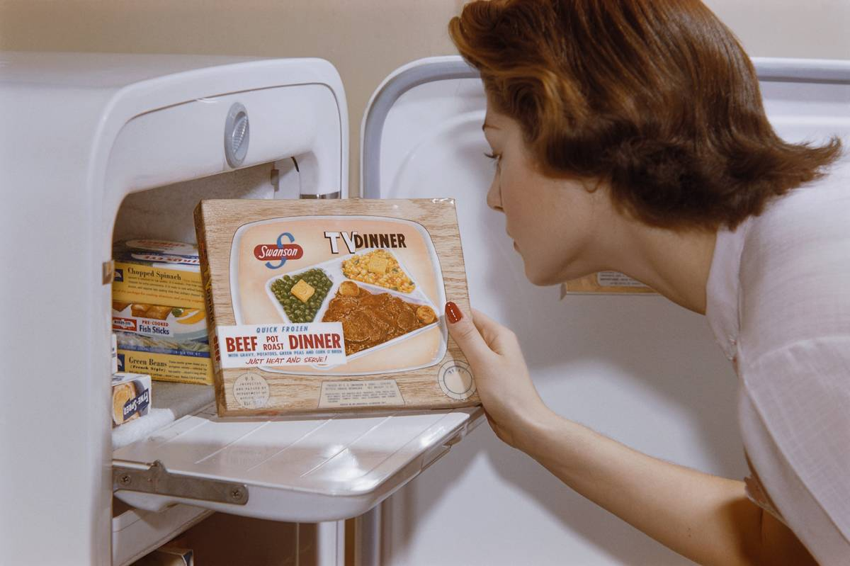 Woman Choosing TV Dinner from Freezer