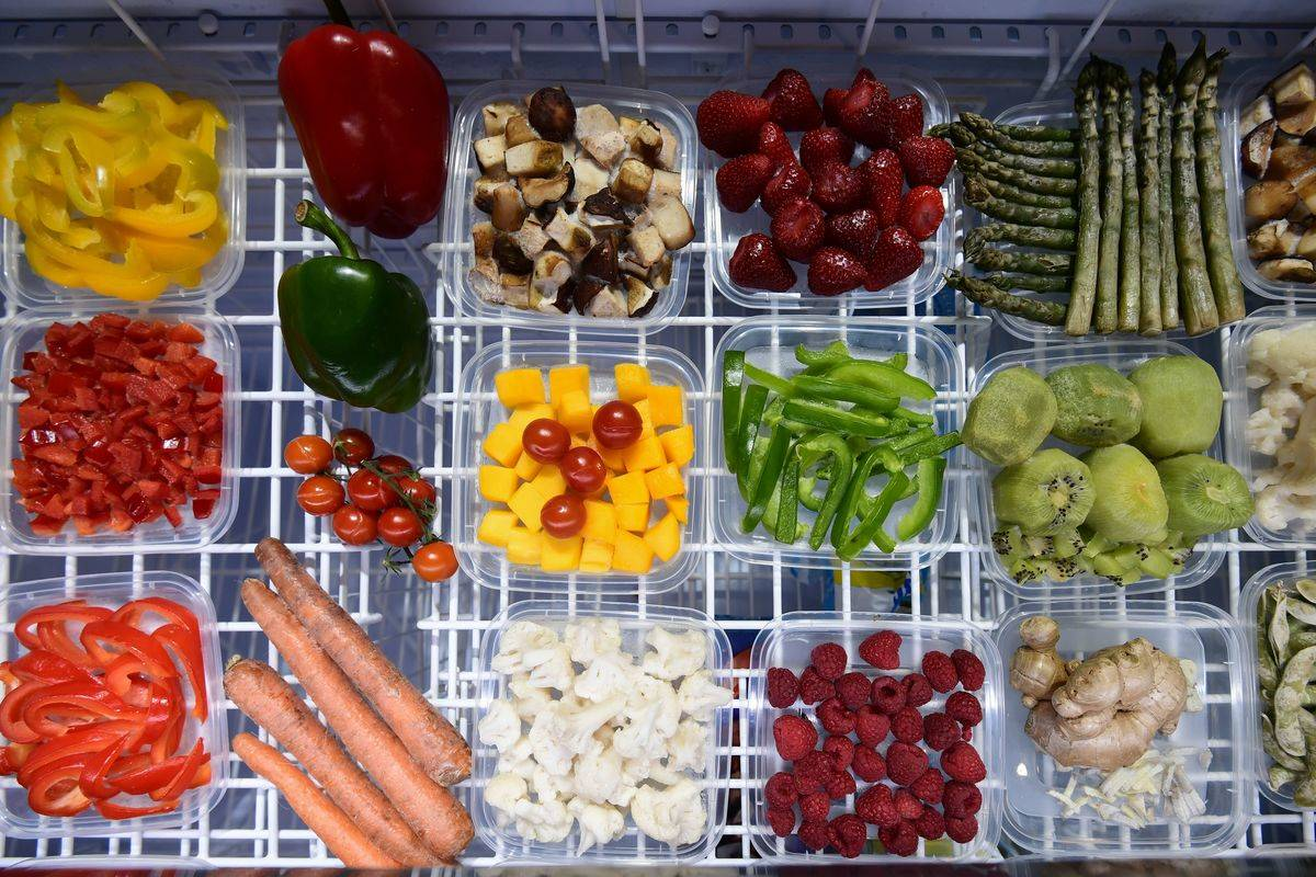 Various fruits and vegetables are organized into square containers.