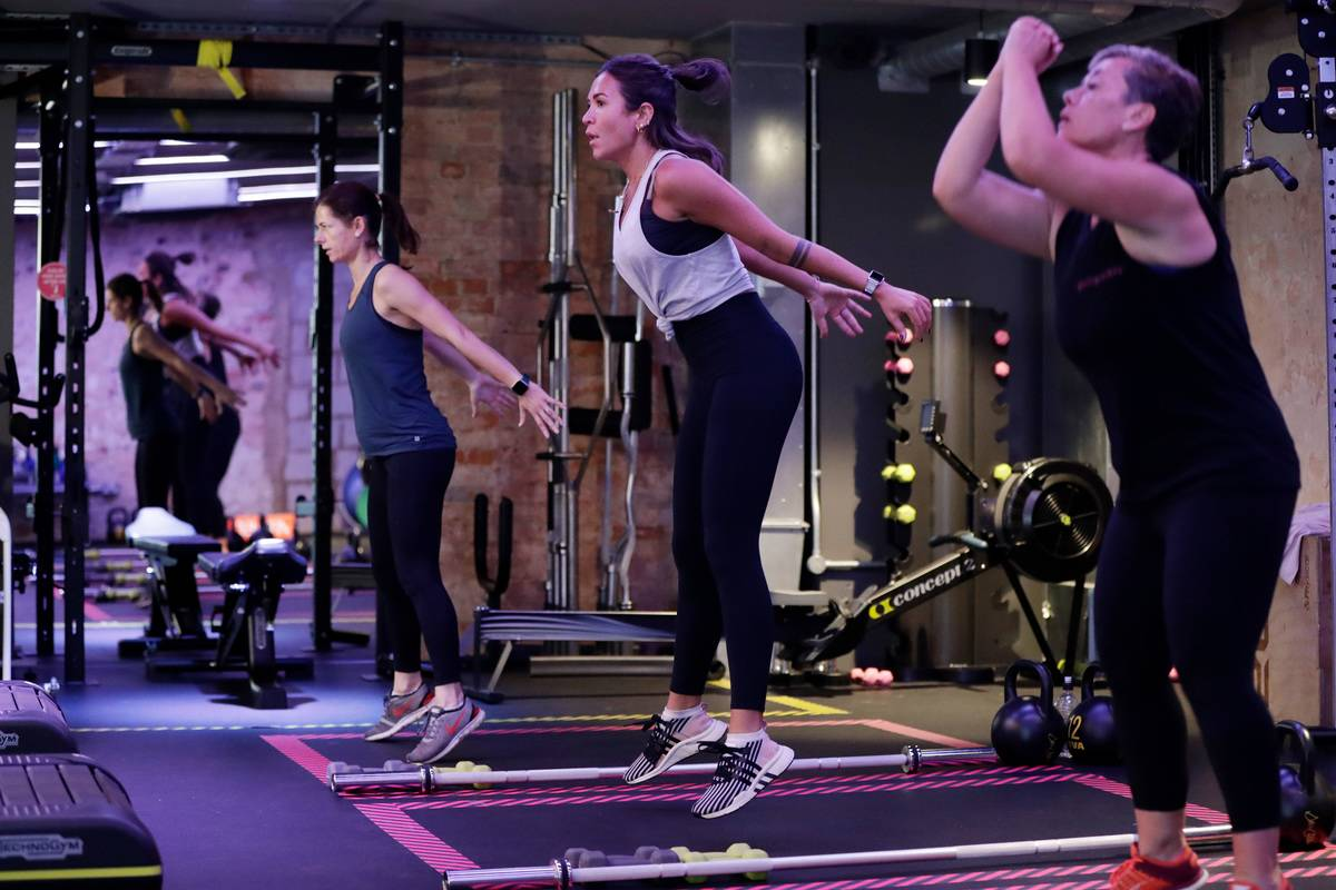 In a boxing class, three women practice a HIIT workout.