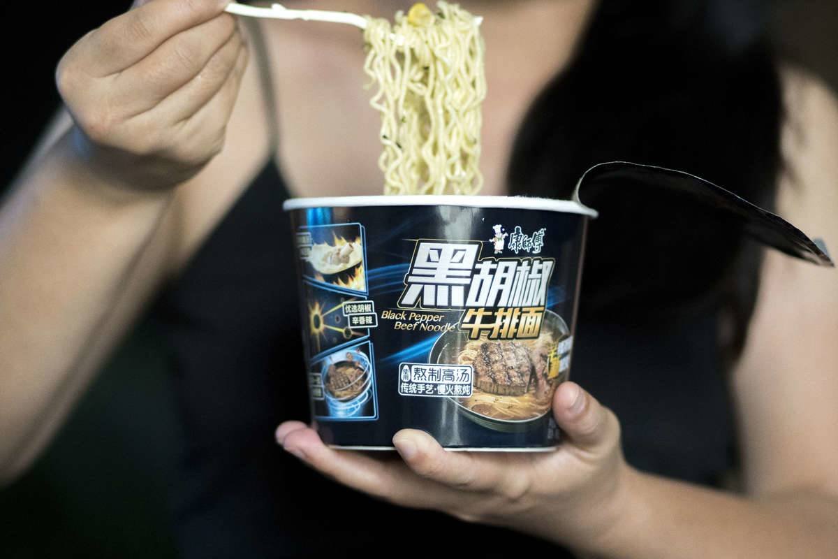 A woman eats instant noodles out of a container.
