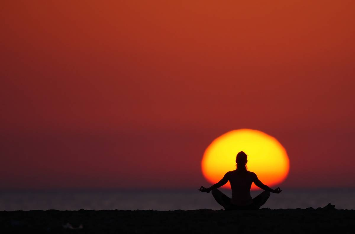 A woman meditates in front of the setting sun.