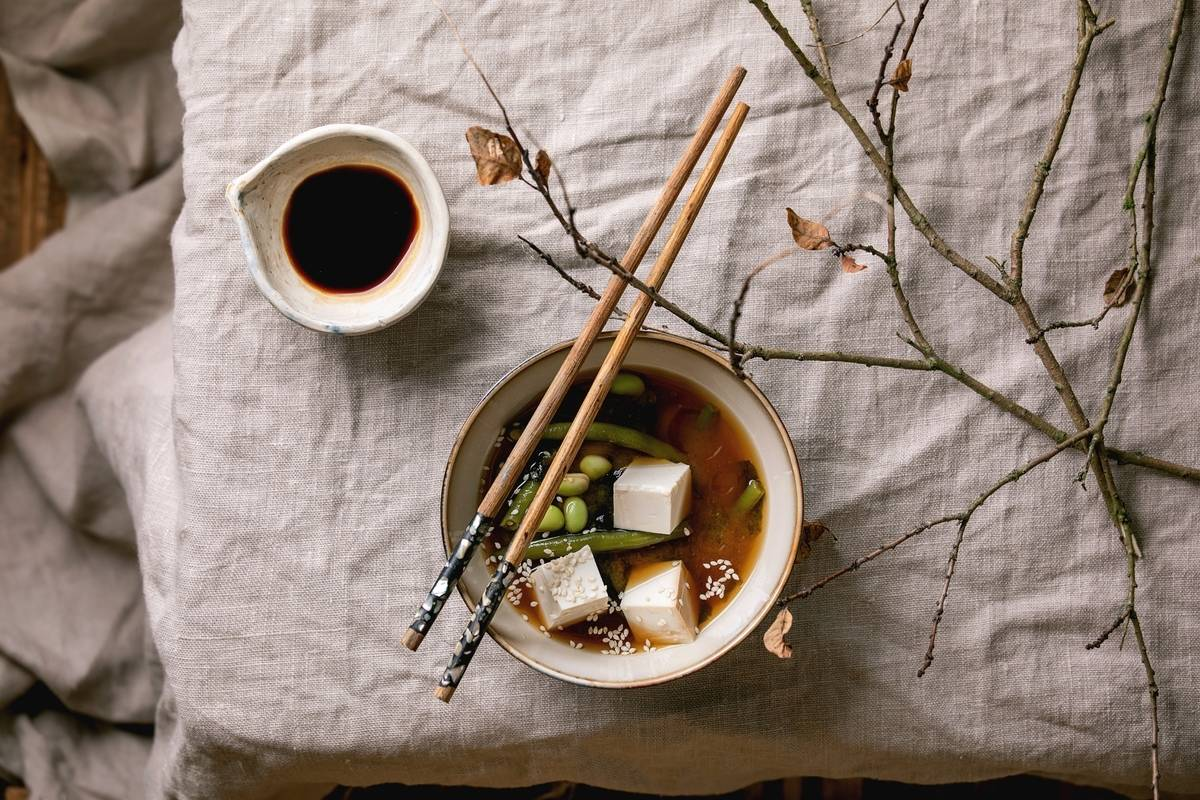 Miso soup sits on a bowl with chopsticks on top of it.