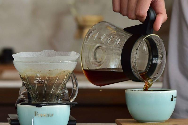 A barista pours coffee into a blue mug.