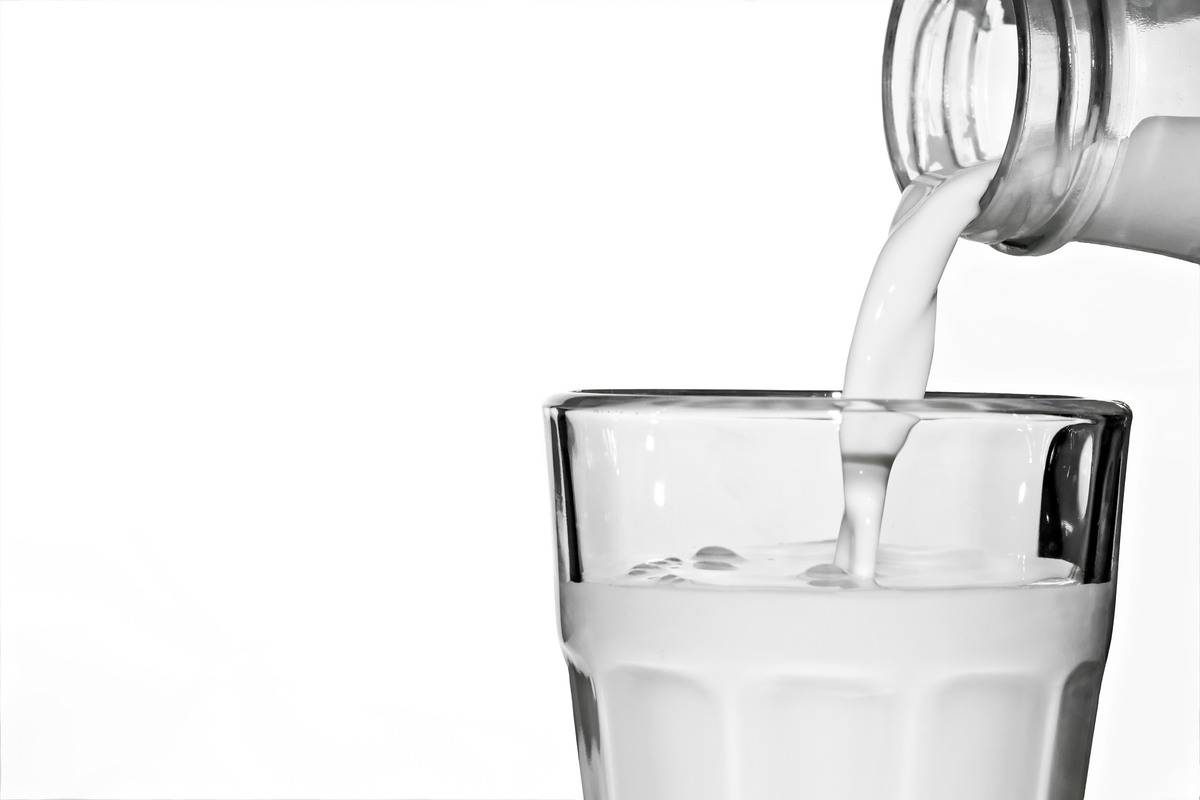 Milk pours from a bottle into a glass.