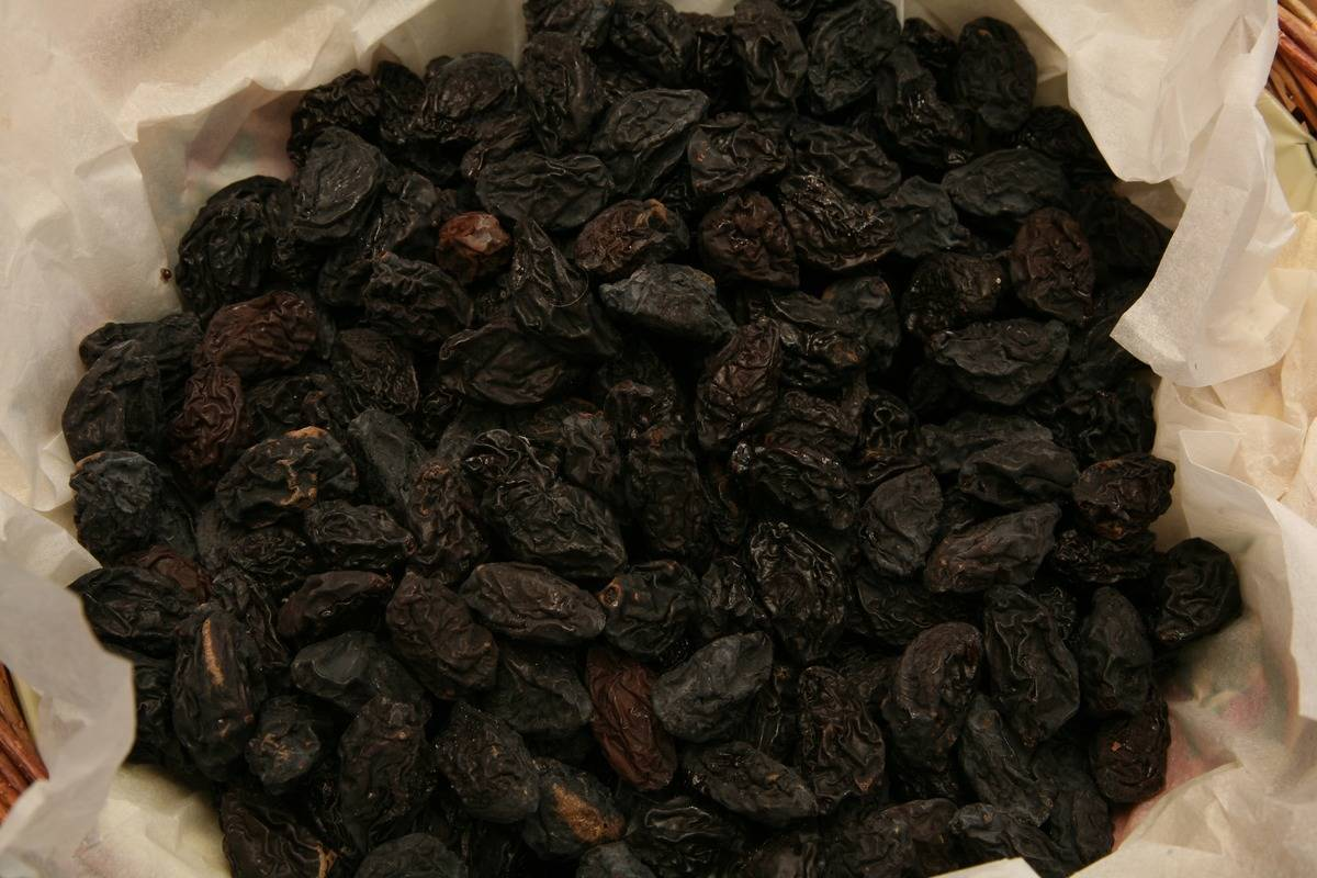 Various prunes are contained in a wax paper bag.