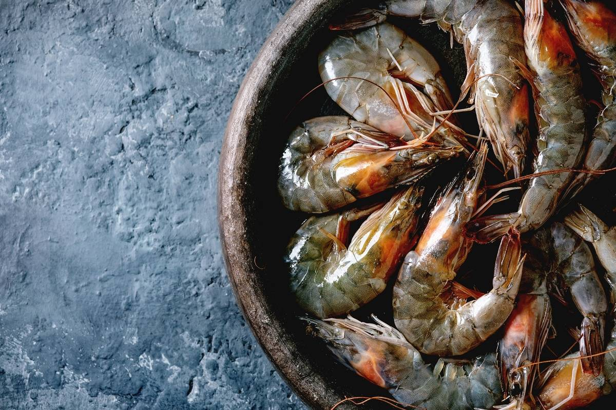 Raw uncooked prawns sit on a clay plate.