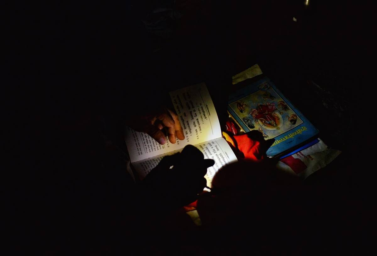 In the dark, a girl reads a book that is illuminated by a flashlight.
