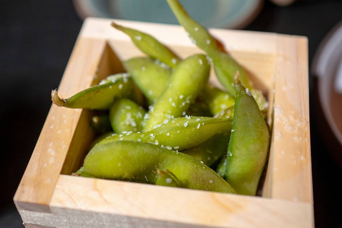 A square wooden container contains salted edamame.