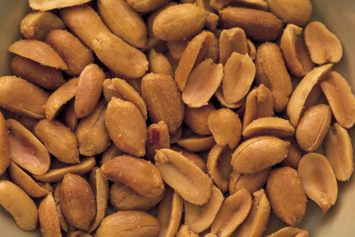 Dozens of salted peanuts sit in a bowl.