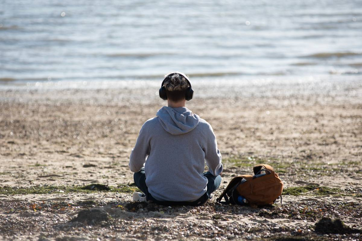 A man sits on the beach with headphones listening to music.