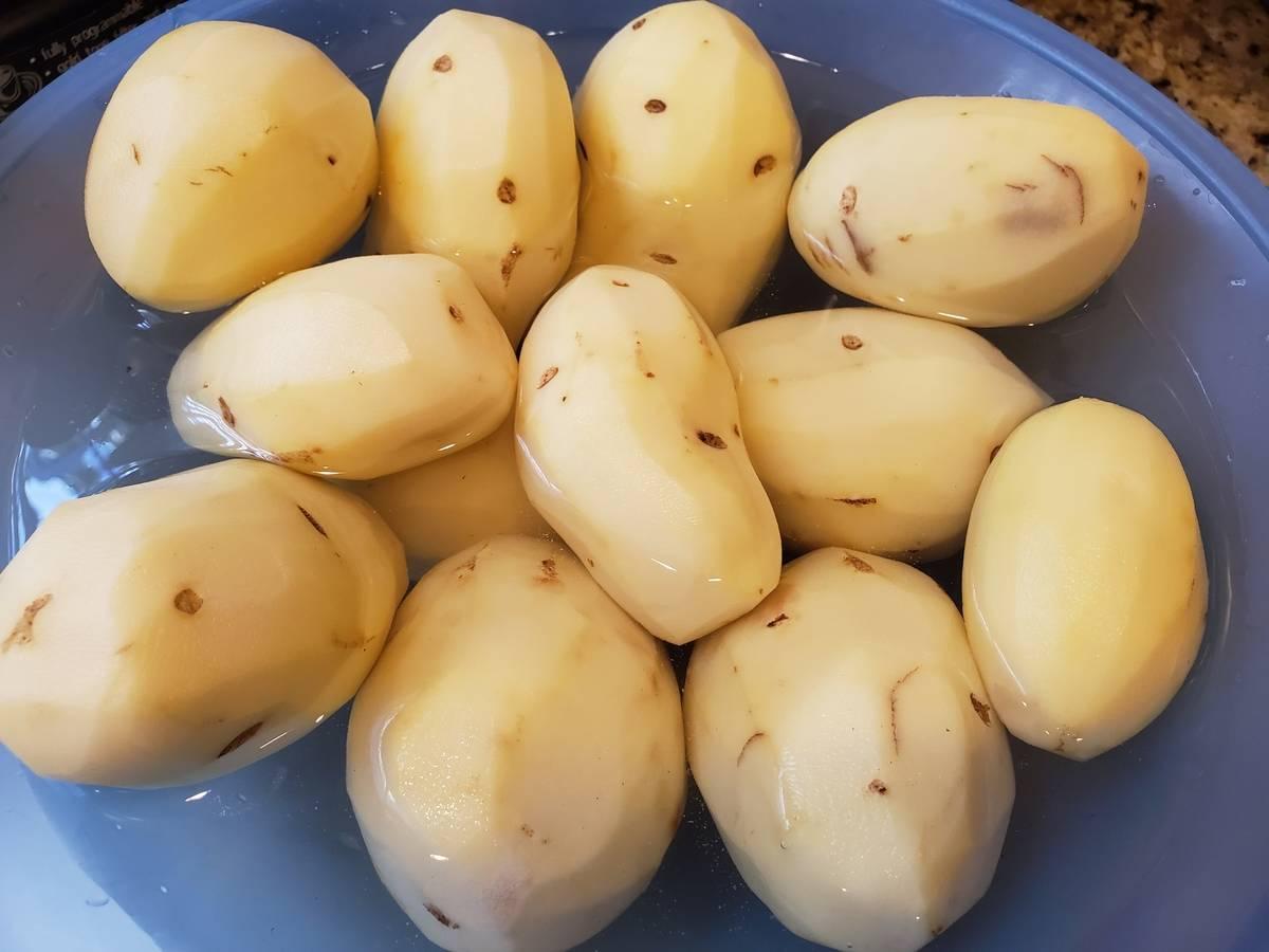 Peeled potatoes soak in water.