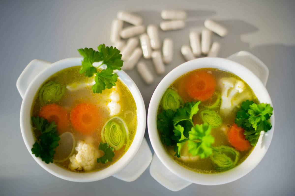 Two bowls of chicken soup sit next to pills.