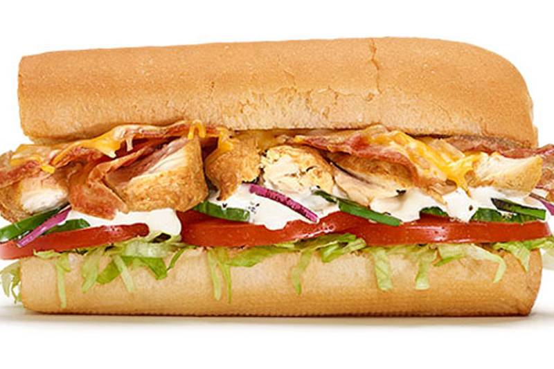 subway chicken and bacon ranch melt sandwich with tomatoes, spinach, and shredded lettuce on a bread roll