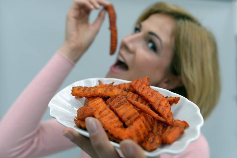 A woman eats sweet potato fries.