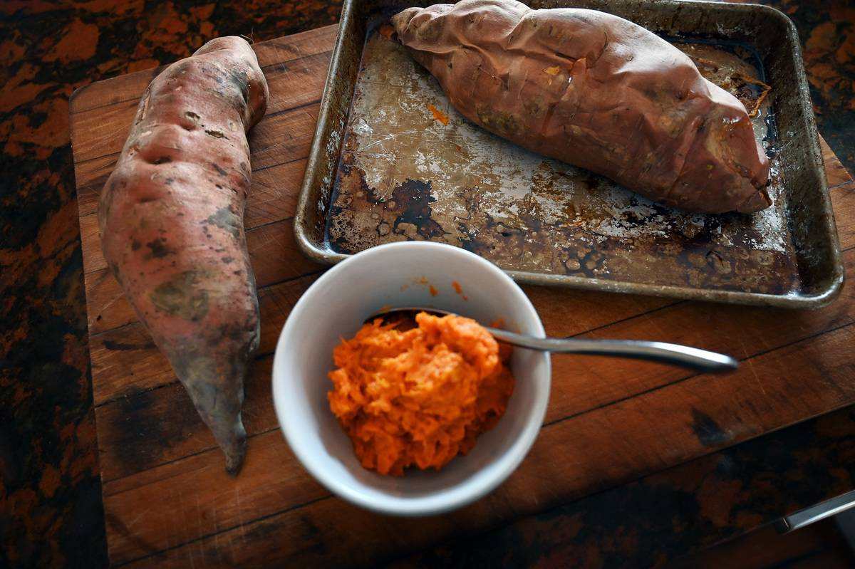 Two whole sweet potatoes lie around a bowl of mashed sweet potatoes.