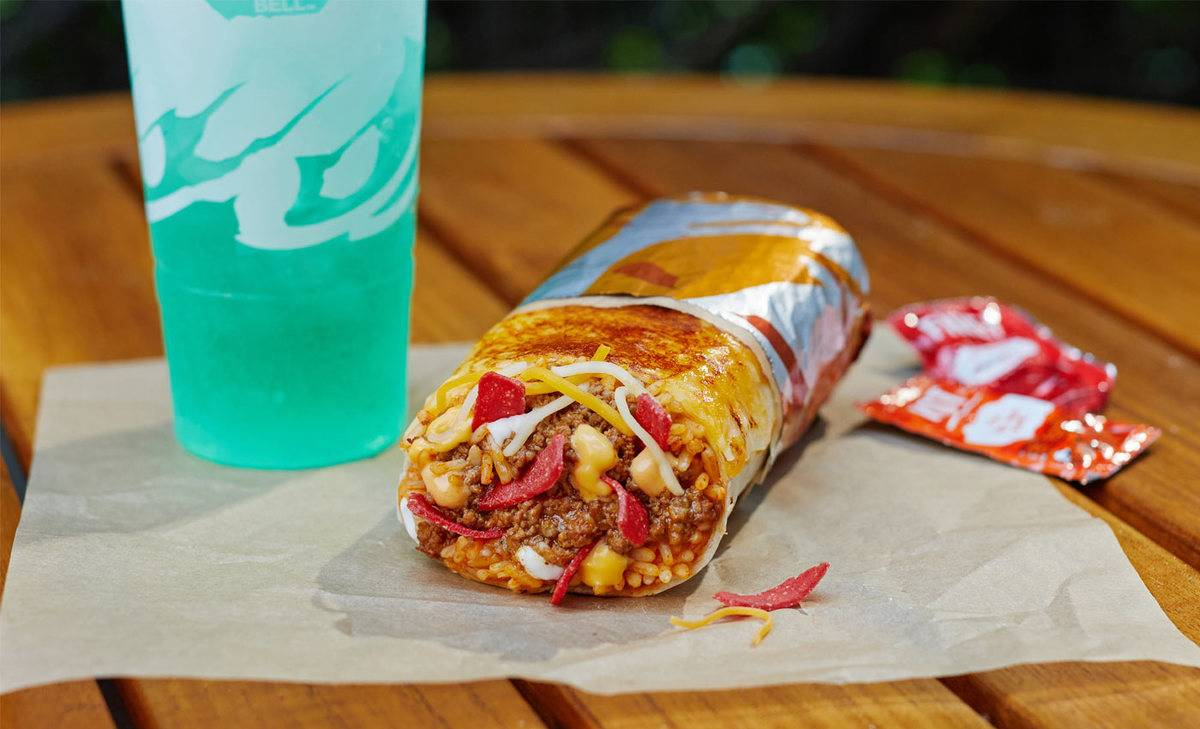 a taco bell grilled cheese burrito with a green drink on a table