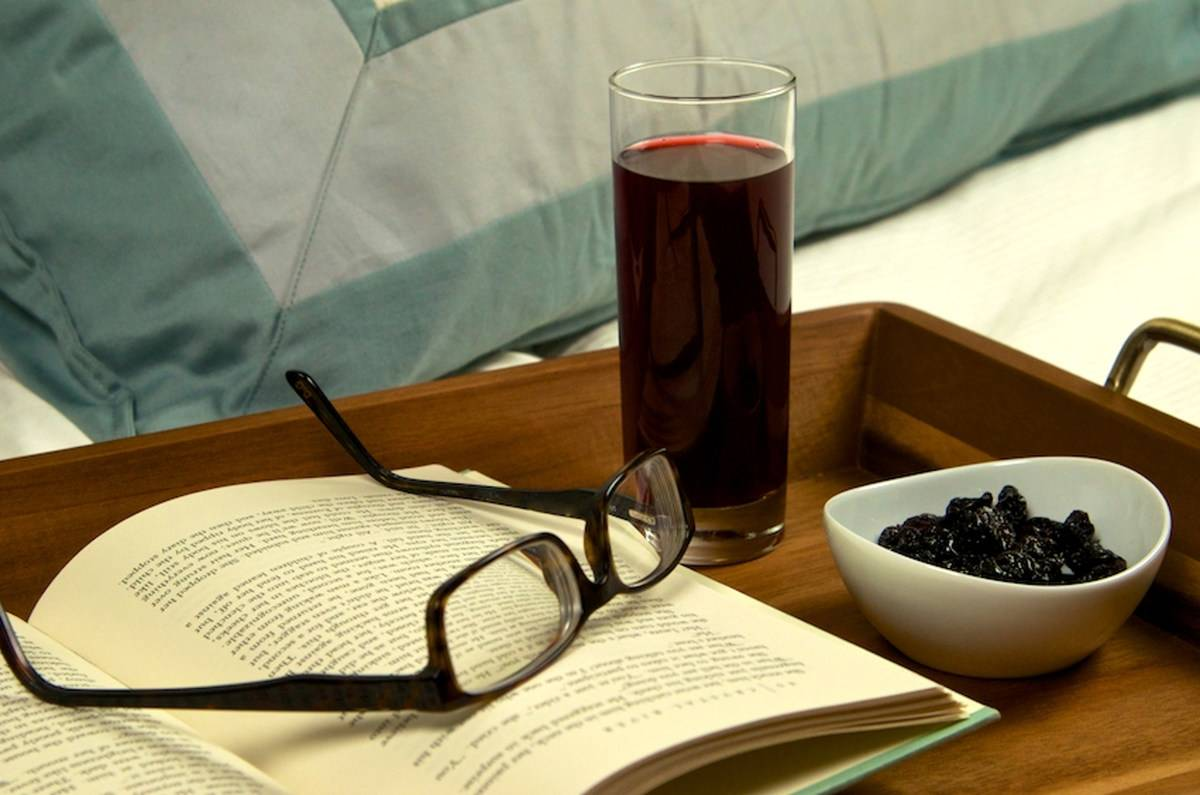 A glass of tart cherry juice sits on a bed tray next to reading glasses and a book.