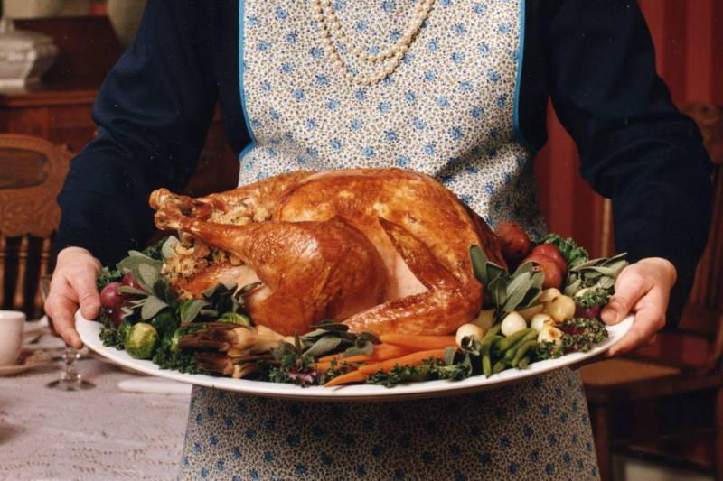 A woman holds a plate of Thanksgiving turkey.