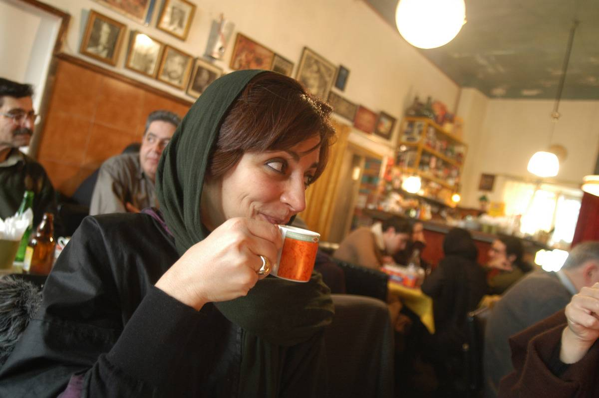 A woman drinks from a small mug of Turkish coffee.
