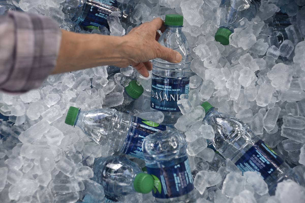 A man picks up a water bottle from an ice tub.