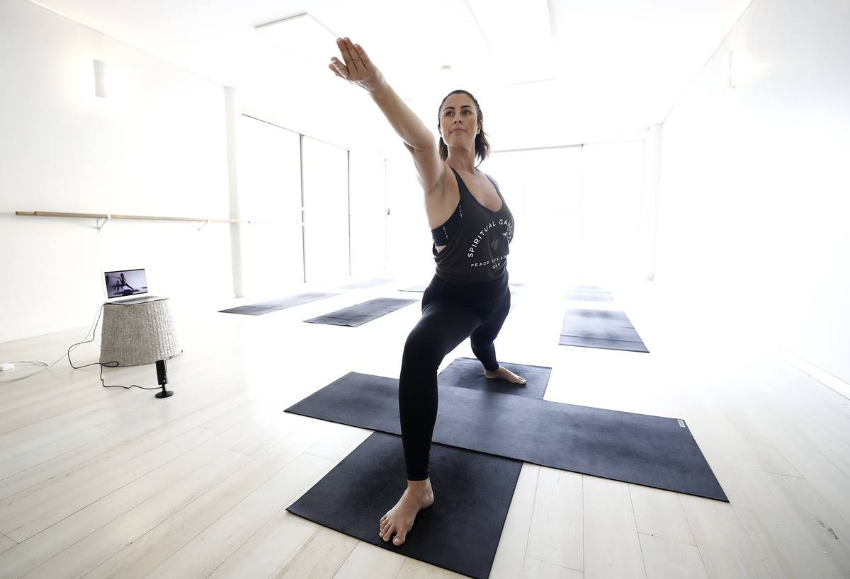 A woman practices yoga in a studio.