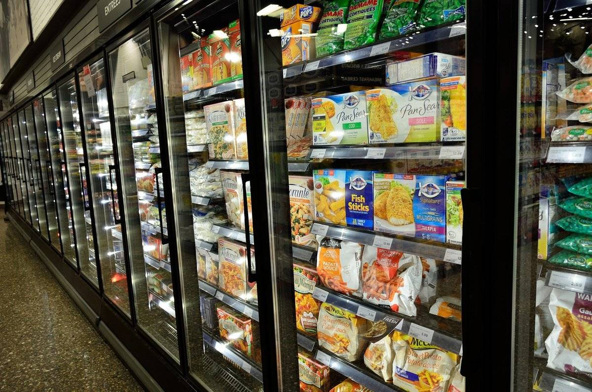 In a grocery store, a refrigerator aisle is stocked with frozen meals.