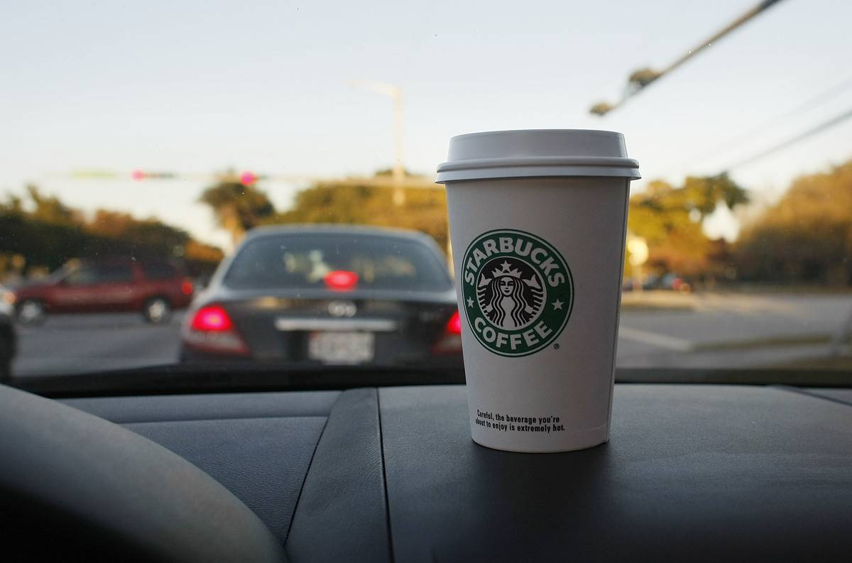 A cup of Starbucks coffee sits on a car's dashboard.
