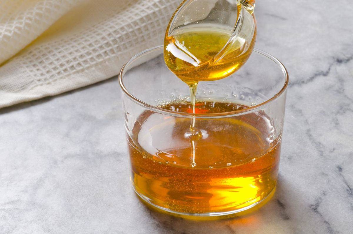 Agave sweetener pours from a smaller cup into a larger glass.