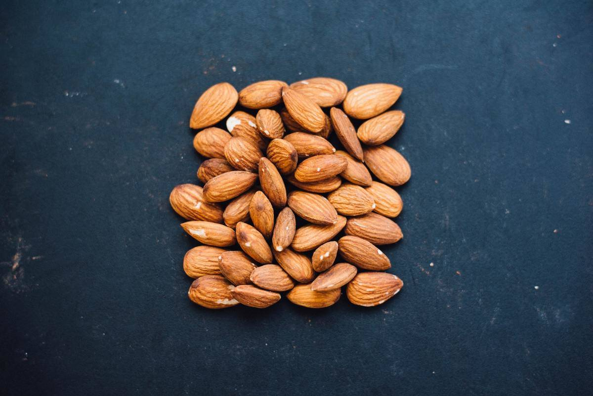 Almonds are arranged in a square against a grey background.
