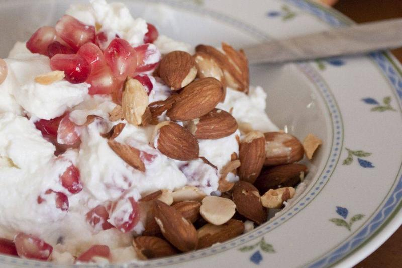 Almonds and pomegranate seeds are in a bowl of yogurt.